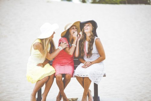 Three happy girls sit on bench
